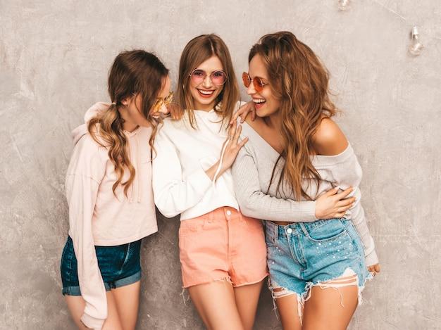 Tre giovani belle ragazze sorridenti in abiti sportivi alla moda estate. posa sexy spensierata delle donne. modelli positivi in occhiali da sole rotondi che si divertono. abbracciare