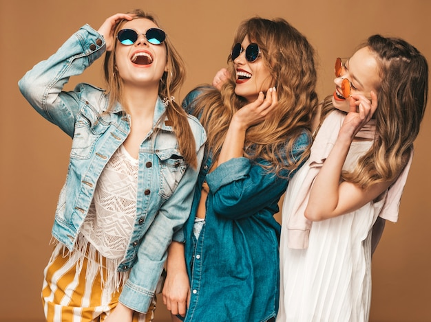 Tre giovani belle ragazze sorridenti in vestiti casuali dei jeans di estate alla moda. posa sexy spensierata delle donne. modelli positivi in occhiali da sole
