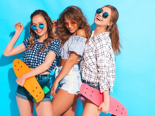 Tre giovani belle ragazze sorridenti sexy alla moda con i pattini variopinti del penny. le donne in estate camicia a scacchi vestiti in posa in occhiali da sole. modelli positivi che si divertono