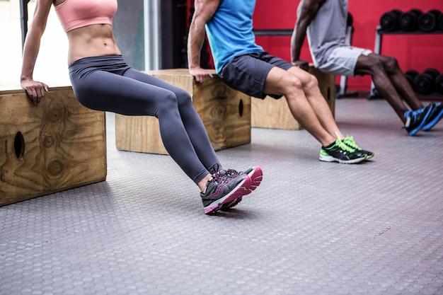 Tre giovani culturisti facendo esercizi