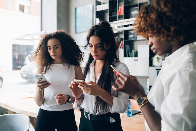 Tre giovani donne di affari multirazziali che guardano lo smartphone in ufficio moderno