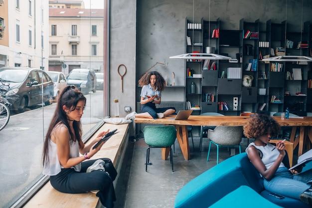 Tre giovani donne di affari multirazziali che lavorano nell'ufficio di coworking moderno