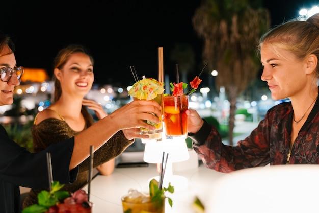 Tre giovani donne fare un brindisi con cocktail su una terrazza di notte