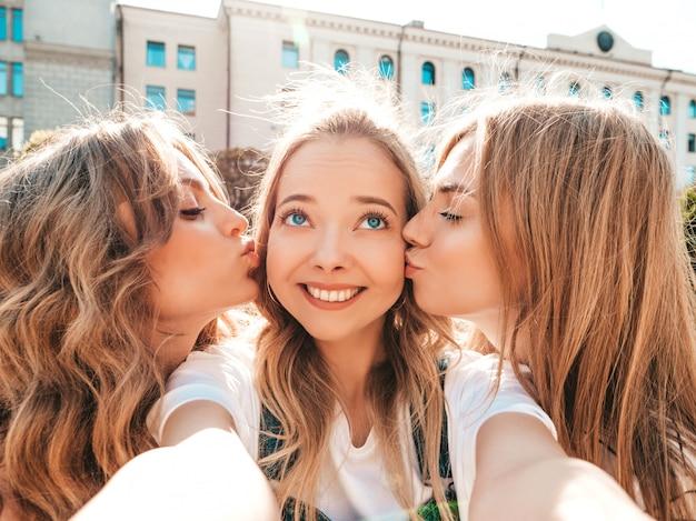 Tre giovani donne sorridenti dei pantaloni a vita bassa in vestiti di estate ragazze che prendono le foto dell'autoritratto del selfie sullo smartphone modelli che posano nella via femminile che bacia il loro amico in guancia