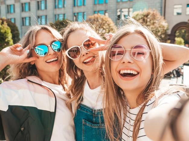 Tre giovani donne sorridenti dei pantaloni a vita bassa in vestiti di estate ragazze che prendono le foto dell'autoritratto del selfie sullo smartphone modelli che posano nella via femminile che mostra le emozioni positive del fronte in occhiali da sole