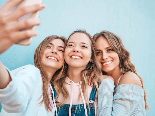Tre giovani donne sorridenti dei pantaloni a vita bassa in vestiti di estate ragazze che prendono le foto dell'autoritratto del selfie sullo smartphone modelli che posano nella via vicino alla parete femmina che mostra le emozioni positive del fronte