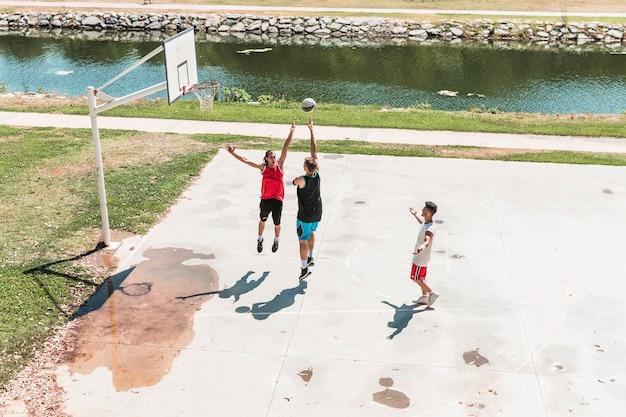 Tre giovani giocatori di sesso maschile a giocare a basket