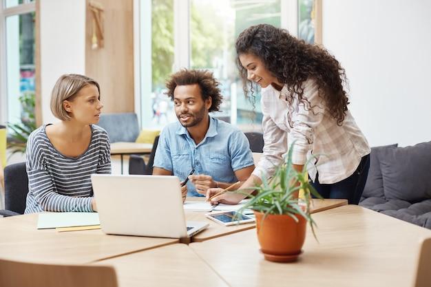 Tre giovani imprenditori potenziali seduti in biblioteca, discutendo i piani aziendali e i profitti dell'azienda, facendo ricerche commerciali con il laptop, guardando attraverso le informazioni sul tablet.