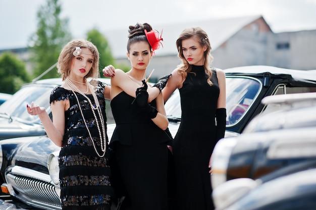 Tre giovani ragazze in abito in stile retrò vicino vecchie auto d'epoca classiche.