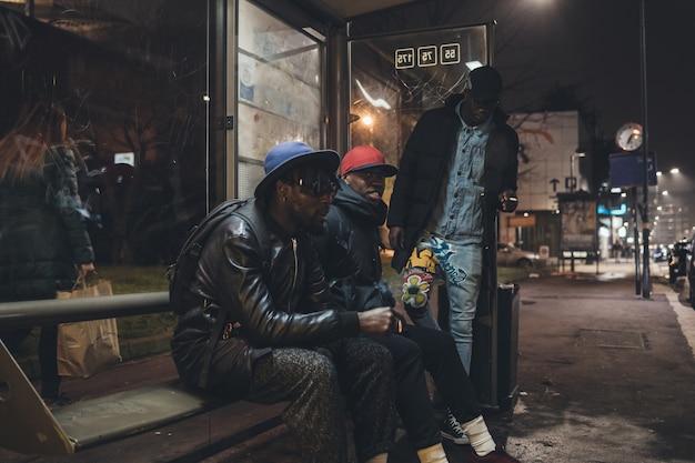 Tre giovani uomini africani che aspettano sulla fermata dell'autobus