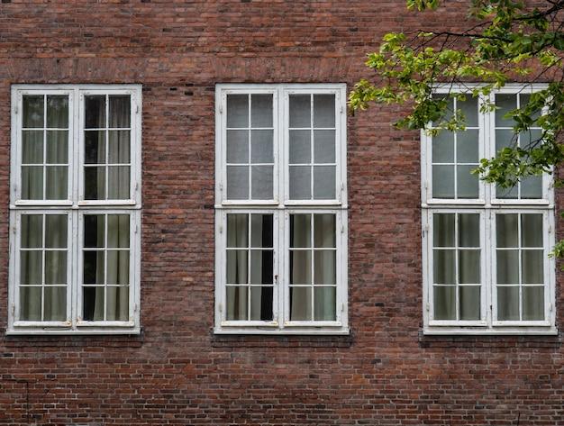 Tre grandi finestre rettangolari con barre di metallo bianco sulla facciata di una vecchia casa di mattoni