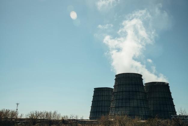 Tre grandi torri di chpp close-up. vapore bianco dall'ampio tubo di chp su cielo blu. enormi tubi della centrale termica producono vapore per l'energia elettrica.