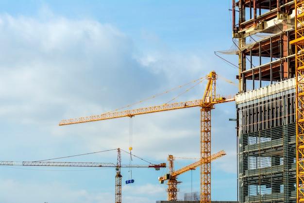 Tre gru da costruzione gialle al lavoro