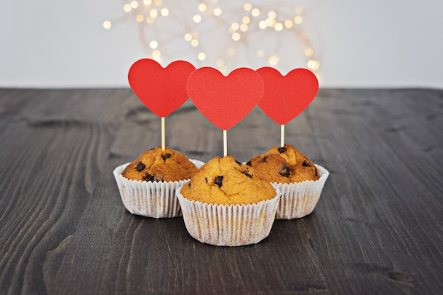 Tre gustosi cupcakes con grandi cuori rossi