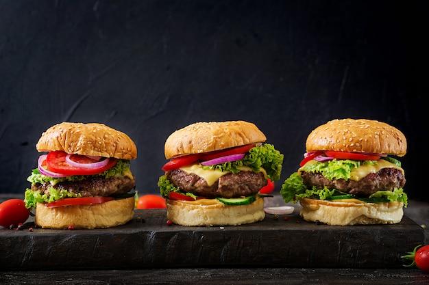 Tre hamburger con hamburger di carne di manzo e verdure fresche su sfondo scuro.