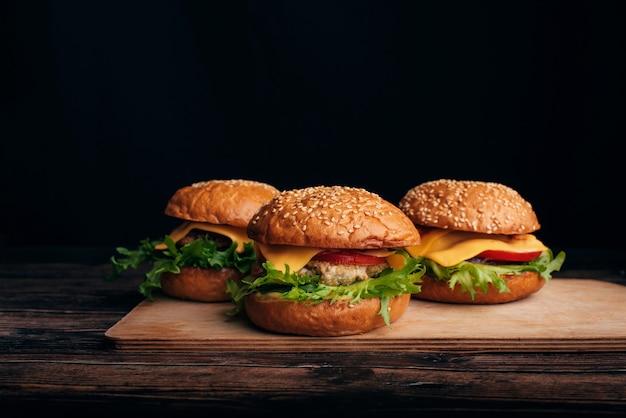 Tre hamburger fatti in casa con carne, formaggio, lattuga, pomodoro su un tavolo di legno