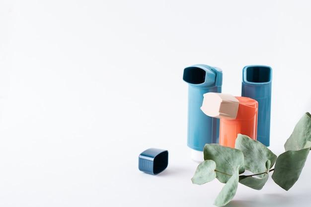 Tre inalatori per l'asma e un ramo di eucalipto su un isolato su bianco. messa a fuoco selettiva.