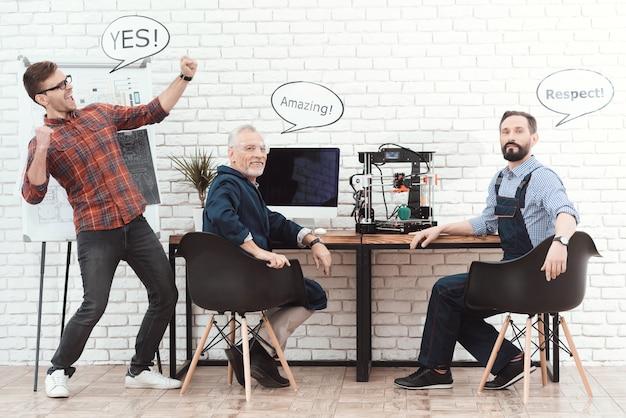 Tre ingegneri lavorano con la stampante 3d in un laboratorio moderno.