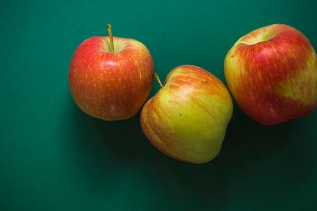 Tre intere mele rosse su sfondo verde