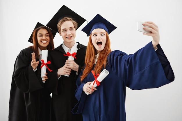 Tre laureati felici allegri che scherzano divertendosi sorridendo facendo selfie con i diplomi in mani, futuri avvocati.