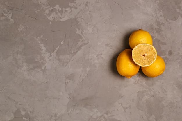Tre limoni sullo sfondo grigio cemento