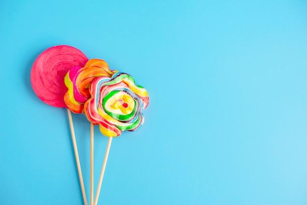 Tre lollipop su uno sfondo blu, copia spazio