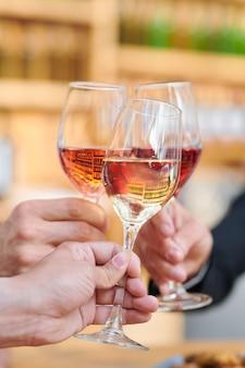Tre mani umane che tengono le bevande alcoliche mentre fanno il pane tostato alla festa congratulandosi a vicenda