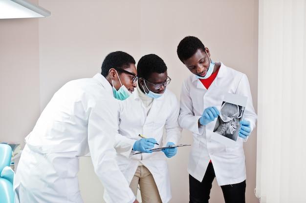 Tre medici maschi che lavorano, discutono con i colleghi in clinica e indicano il cranio a raggi x.
