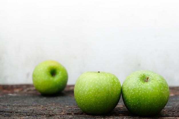 Tre mele verdi fresche disposte sul legno