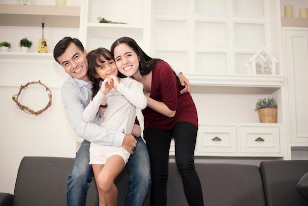 Tre membri della famiglia felice in buon umore con abbraccio