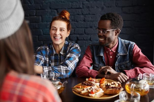Tre migliori amici che godono di una piacevole conversazione durante il pranzo nel moderno bar interno