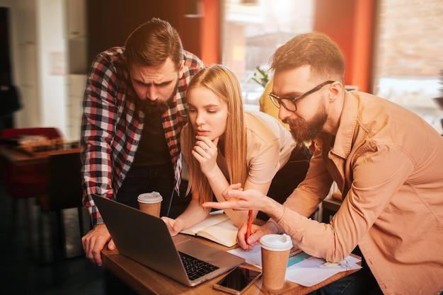 Tre migliori amici sono in piedi vicino al tavolo con il computer e guardano lo schermo. uno di questi sta puntando sullo schermo. gli altri due lo ascoltano attentamente.