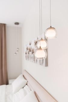 Tre moderne lampade in vetro trasparente a forma di palline su lacci sottili.