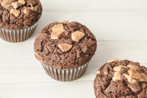 Tre muffin al cioccolato allineati in diagonale nel fondo bianco.
