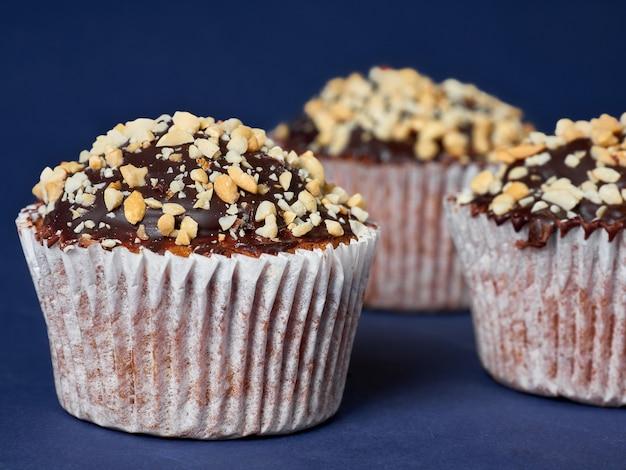 Tre muffin con arachidi e glassa al cioccolato in linea su sfondo blu.