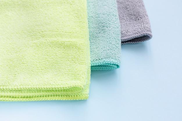 Tre nuovi tessuti piegati in microfibra per la pulizia su sfondo blu. pulizia di asciugamani in micro tessuto per spolvero e lucidatura. concetto di servizio di pulizia domestica. primo piano, copia spazio