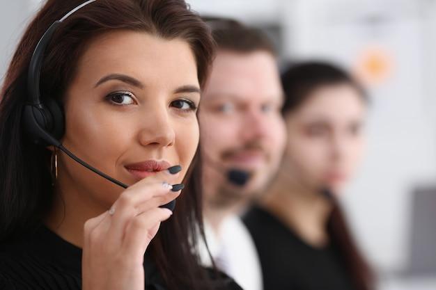 Tre operatori di servizi di call center nel centro assistenza del team di lavoro