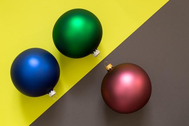 Tre palle dell'albero di natale su una parete multicolore