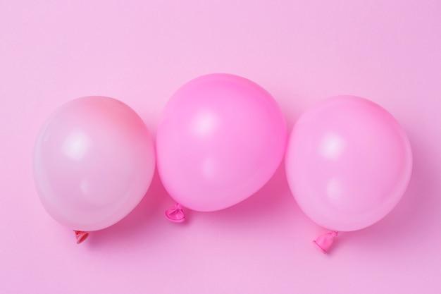 Tre palloni su un primo piano del fondo di rosa pastello, concetto di festa
