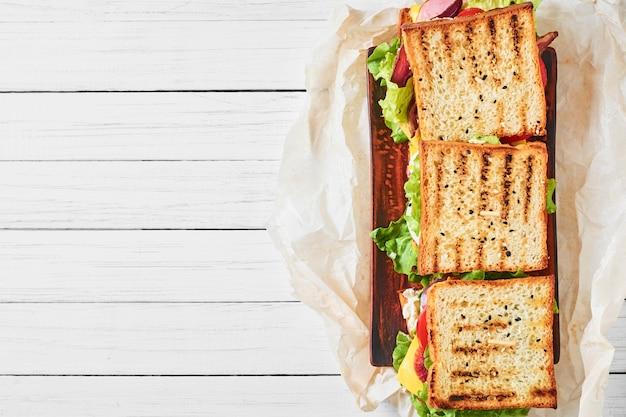 Tre panini con prosciutto, lattuga e verdure fresche su uno sfondo bianco