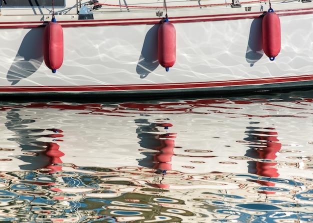 Tre parafanghi rossi appesi sopra lo scafo di una barca