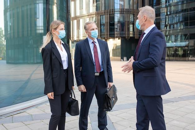 Tre partner commerciali di contenuti in maschere che discutono di affare all'esterno. manager di successo fiduciosi in piedi per strada e al lavoro durante la pandemia di coronavirus. negoziazione e concetto di partenariato