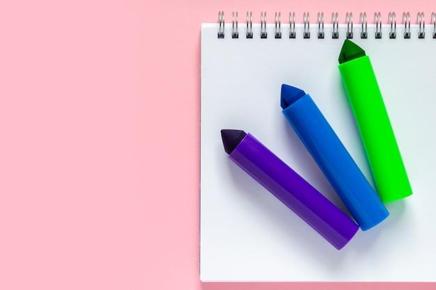 Tre pennarelli multicolori su un foglio bianco di una lavagna con una spirale su uno sfondo rosa delicato. posto per il testo. torna al concetto di scuola