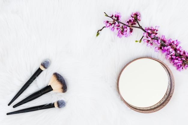 Tre pennelli trucco con specchio rotondo e ramoscello fiore artificiale su sfondo di pelliccia bianca