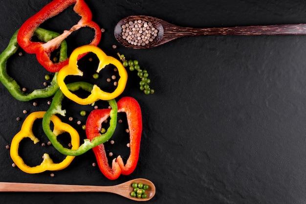 Tre peperoni dolci su un fondo di legno, cucinando insalata di verdure