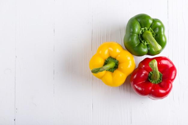 Tre peperoni freschi sul tavolo bianco.