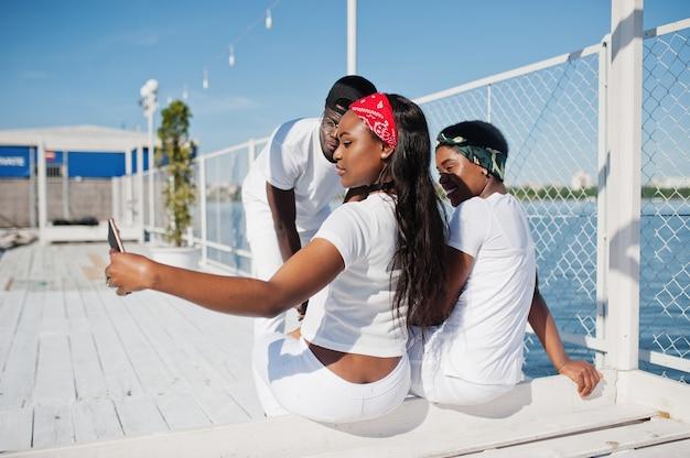 Tre persone afroamericane eleganti e alla moda, indossano abiti bianchi contro il lago sulla spiaggia del molo che fanno selfie. moda di strada di giovani amici neri.