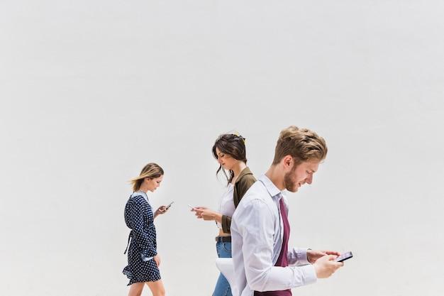 Tre persone che camminano su sfondo bianco utilizzando il telefono cellulare