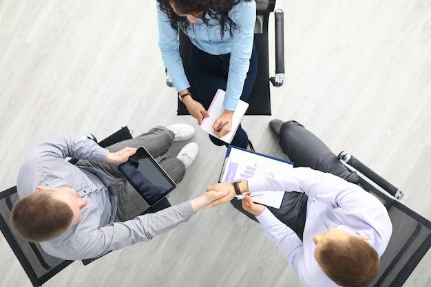 Tre persone si siedono su una sedia in cerchio vista dall'alto e discutono di lavoro.