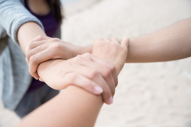 Tre persone si uniscono le mani